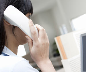 事務所で電話を受ける女性