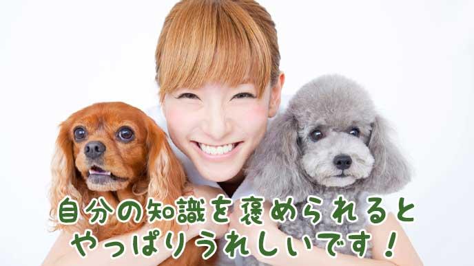 微笑みながら両脇で子犬を抱く獣医師の女性