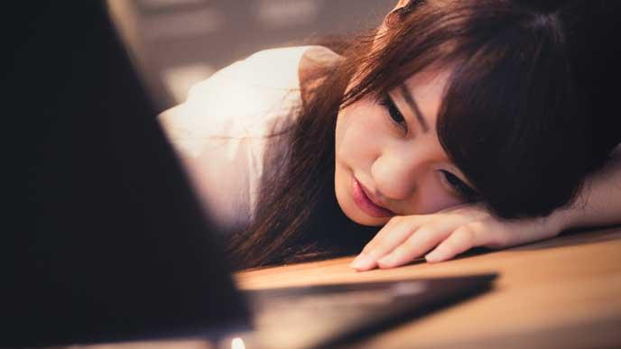 残業で疲れてデスクに倒れかかる会社員の女性