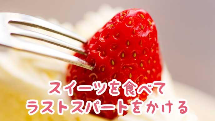 ケーキに乗っかった苺にフォークを刺す