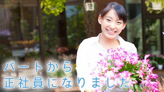 お花を持ちニッコリ微笑むフラワーショップの正社員
