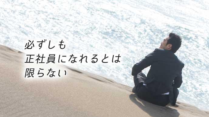 砂浜に座り海を眺める契約社員