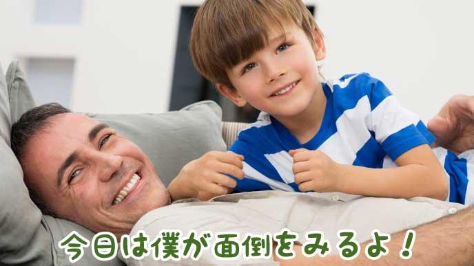 笑顔でソファに寝転がる父親と子供