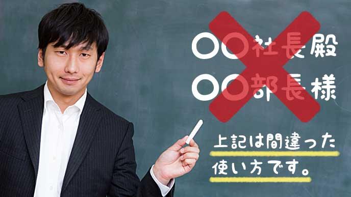 黒板に書いてある役職と敬称の使い方を説明する教師