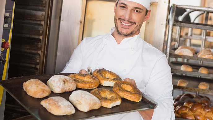 焼き上げたパンを運ぶパン職人