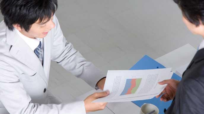 同僚から仕事の資料を受け取るビジネスマン