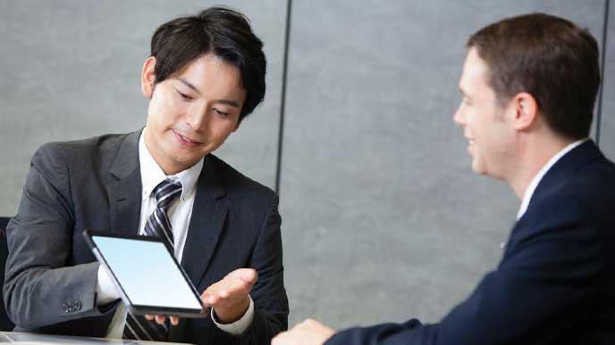 外国人ビジネスマンに社内商品であるタブレットPCの説明をする会社員