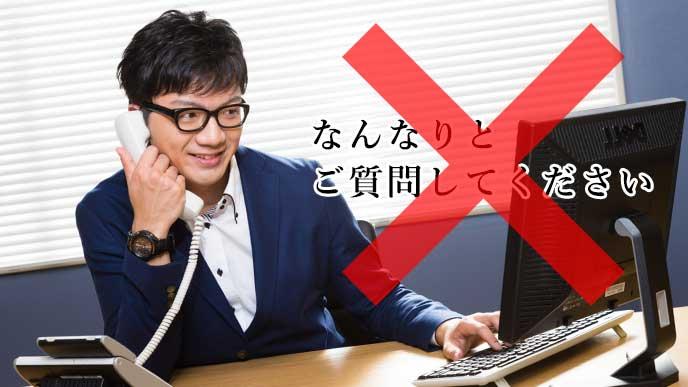 パソコンのモニターを見ながら電話応対をする会社員