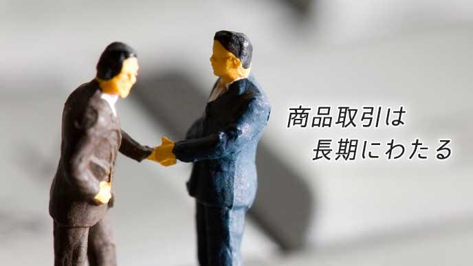 握手をしているビジネスマン達の人形