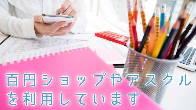 ペン立てとピンクのファイルが置かれたデスクで仕事をしている会社員の女性