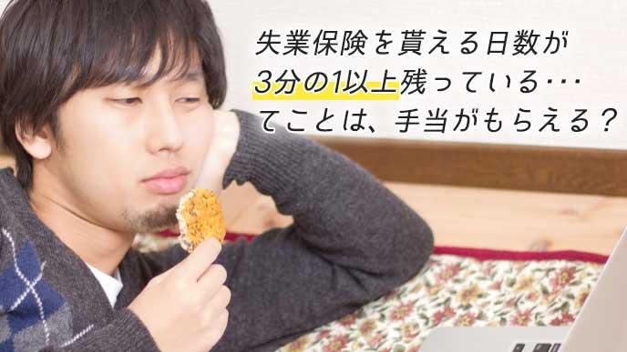 自宅で横になりながらせんべいを食べる男性