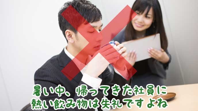 同僚の営業マンに熱い緑茶を差し出すOL