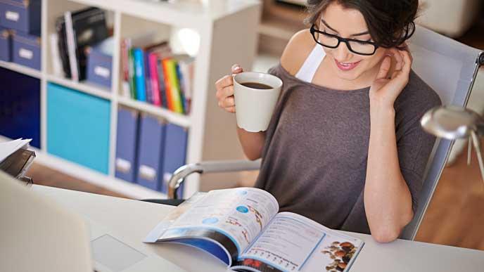 オフィスでコーヒーを飲みながら雑誌を読む女性