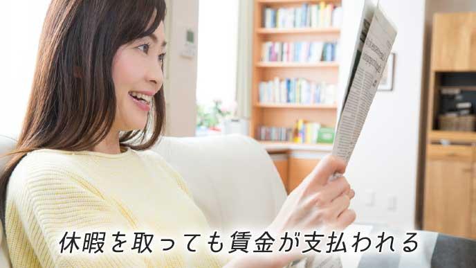 ソファに座り新聞を読んでいる女性