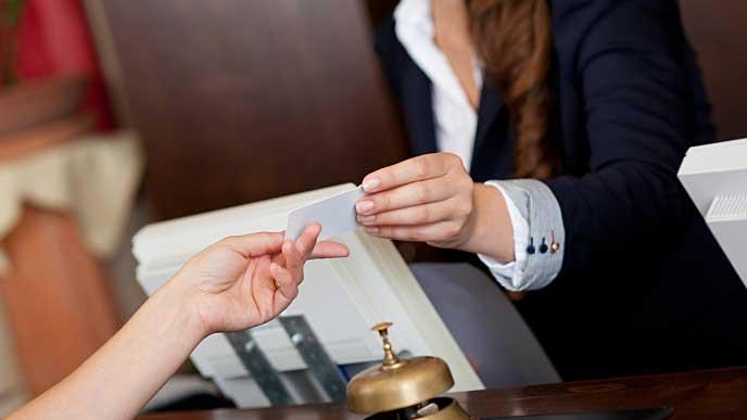 受付でお客様からカードを受け取るレセプショニスト