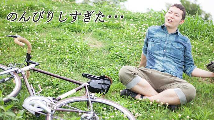 自転車を倒して野原で休息を取っている男