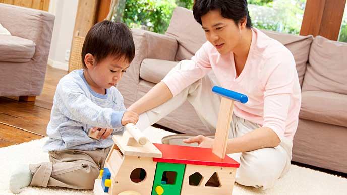 木のおもちゃで子供と一緒に遊ぶ父親