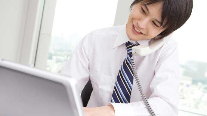 取引先と電話をしながらパソコンを使い仕事をしているビジネスマン