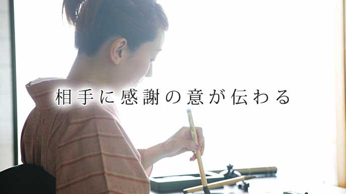 筆を持ち書道をしている女性