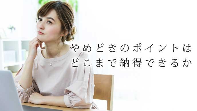 机に座って考え事をしている女性