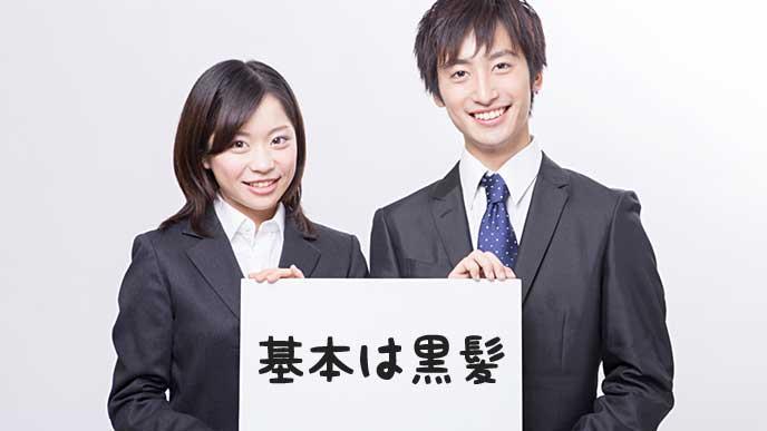 メッセージボードを持ったスーツ姿の男性と女性