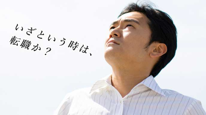 疲れた表情で空を見上げているサラリーマン
