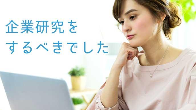 ノートパソコンを見ながら憂鬱そうな表情をしている女性