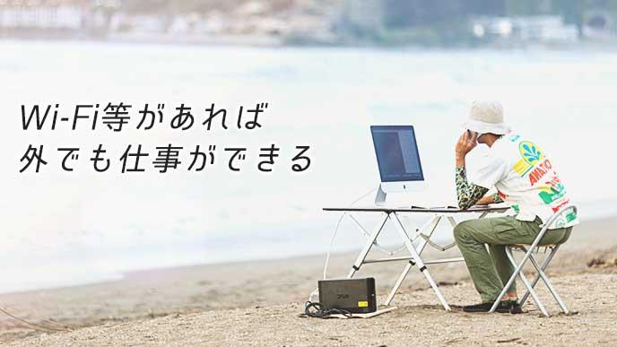 海辺で仕事をしているノマドワーカー