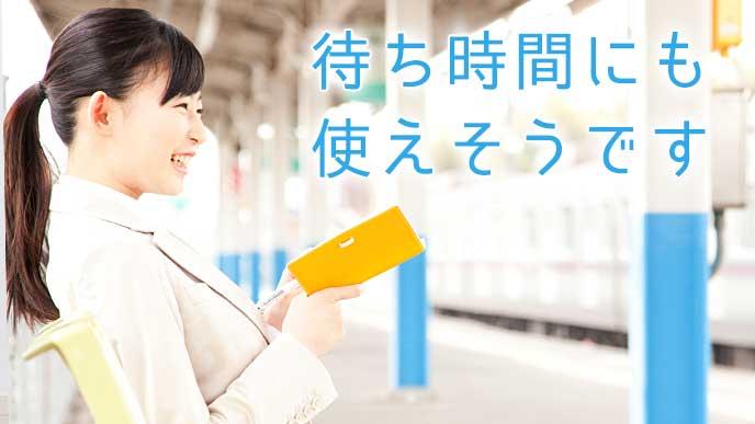 駅のホームで読書をしているOL