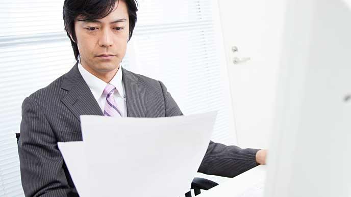 険しい表情でエントリーシートを見ている採用担当者の男性