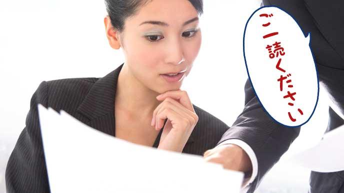 同僚から渡された資料を確認している女性社員