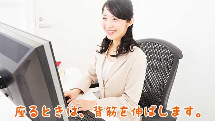 背筋を伸ばして仕事をしている会社員の女性