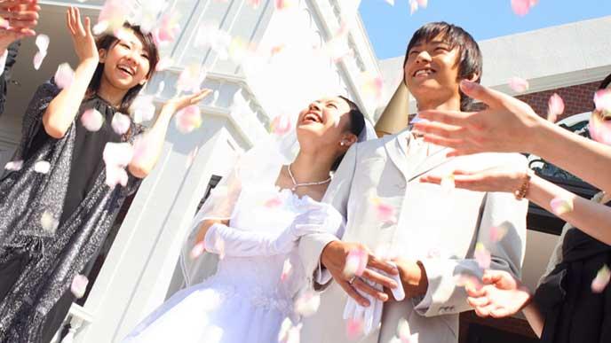 結婚式で皆に祝福される新郎新婦