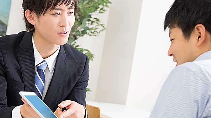 取引先の相手にタブレットPCの画面を見せているビジネスマン