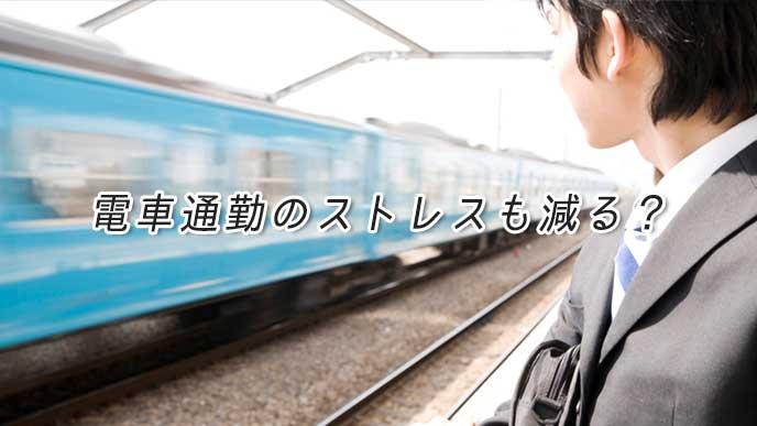 駅のホームで通勤用の電車を待っているサラリーマン