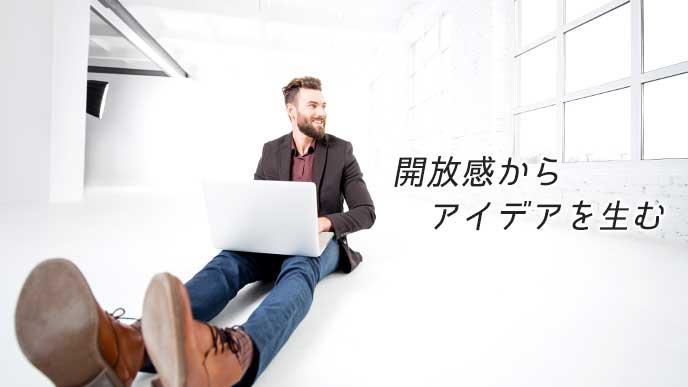明るく広い部屋でノートパソコンを使っている男性