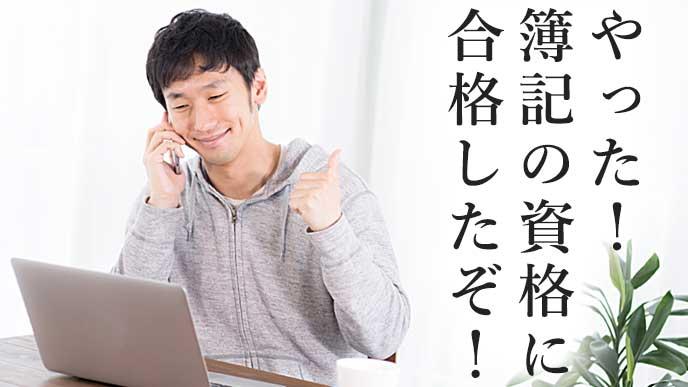 ノートパソコンを見ながら電話をして喜んでいる男性