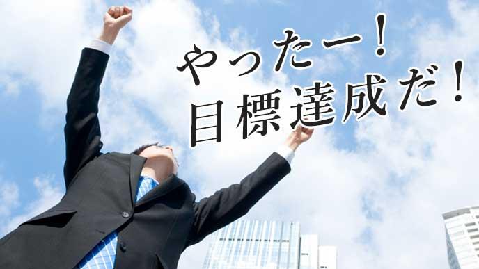 空に向かってガッツポーズを取るビジネスマン