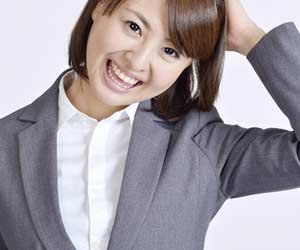 頭に手をやりながら照れ笑いする女性