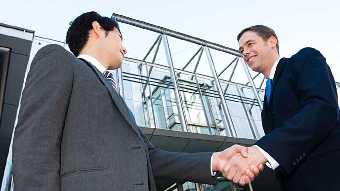外国人の同僚と握手をしているビジネスマン