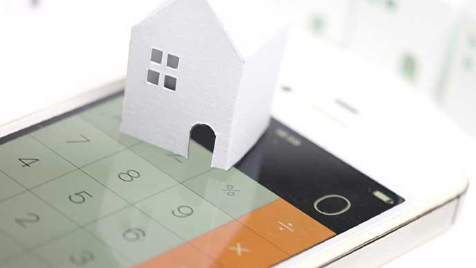 電卓アプリを表示しているスマホとペーパークラフトで作られた家