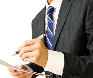青系のネクタイでメモをとるビジネスマン