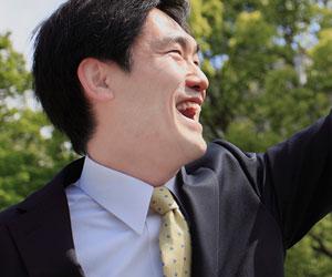 緑系のネクタイで笑顔のビジネスマン