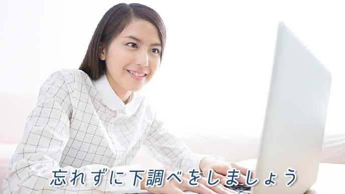 ノートパソコンで調べものをしている女性