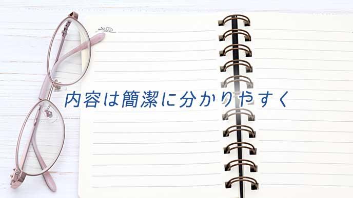 眼鏡とページを開いたノート