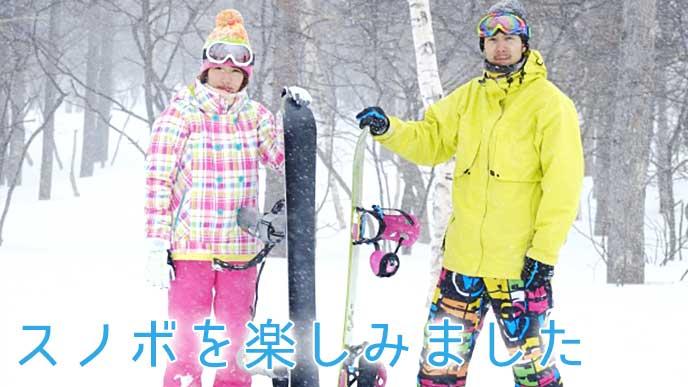 スキー場でスノボを立てている男女