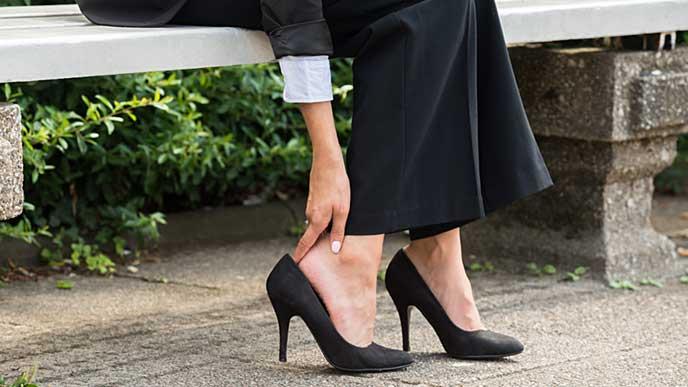 靴擦れで踵を押さえているヒールを履いた女性