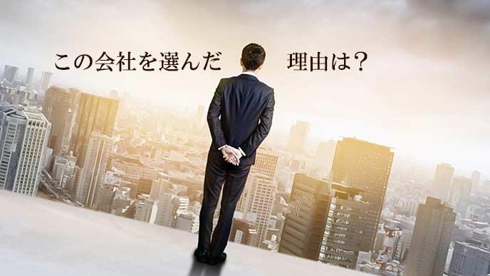 屋上からビルを見渡すビジネスマン