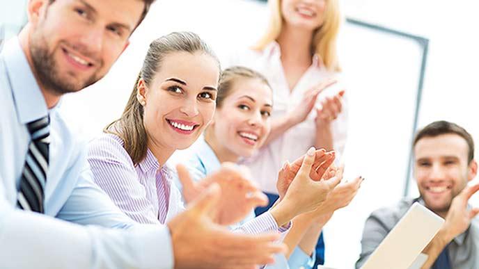 拍手する同僚の男女社員