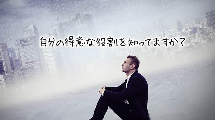 雨に打たれながら宙を見つめる男性